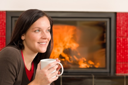 Young woman enjoying winter hot drink by home fireplace Stock Photo - 11476120