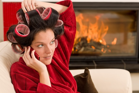 Home beauty woman with curlers calling phone fireplace red bathrobe Stock Photo - 11476131