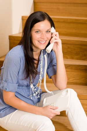 Home living happy young woman calling phone sitting on staircase photo