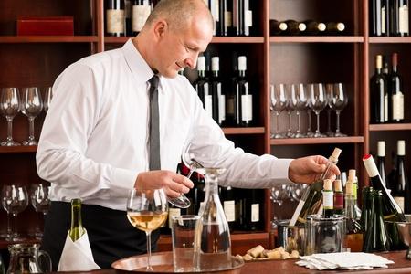 bartender: At the bar - waiter hold bottle white wine in restaurant