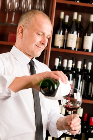 degustation: At the bar - waiter pour red wine in glass restaurant