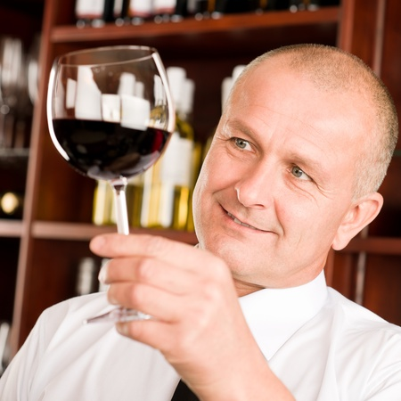 Waiter at bar hold glass of red wine in restaurant photo