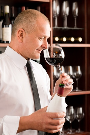 Waiter at bar smell glass of red wine in restaurant photo
