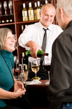 Wine bar senior couple enjoy drink smiling barman pour glass photo