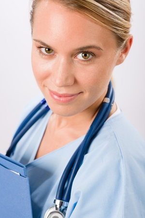 Attractive female doctor standing with stethoscope and folders isolated portrait Stock Photo - 11604330