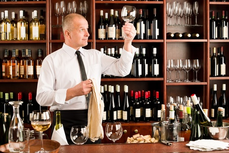 behind bars: Wine bar waiter looking at clean glass in restaurant