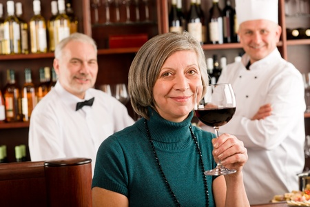 Restaurant manager happy taste glass of red wine in bar photo