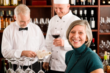 restaurant staff: Restaurant manager smiling with staff at wine bar