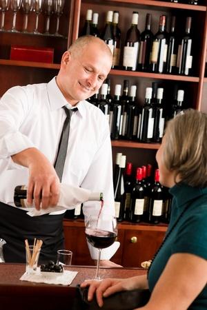 Wine bar professional waiter serve glass senior woman smiling photo