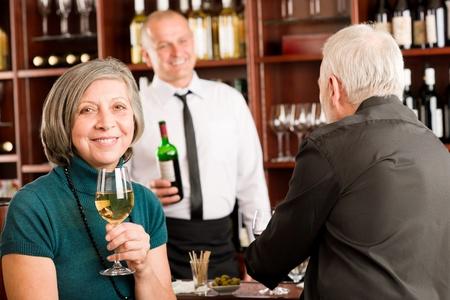 Wine bar senior couple enjoy drink smiling barman discussing photo