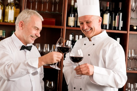 Chef cook and waiter toasting with wine smiling in restaurant photo