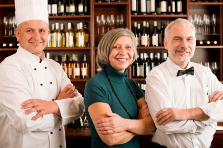 restaurant staff: Restaurant manager posing with chef cook and waiter wine bar