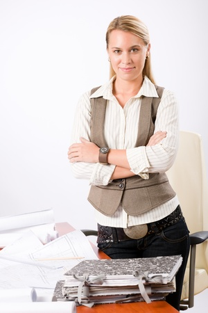 architectural studies: Attractive young architect woman with sketches behind office desk