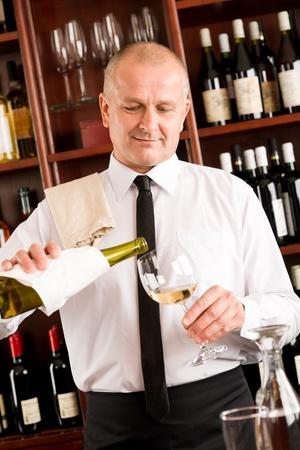 Wine bar happy waiter pour white wine in glass restaurant photo