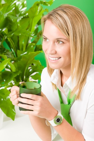 environment friendly: Green business office woman drink coffee plant environment friendly smile Stock Photo