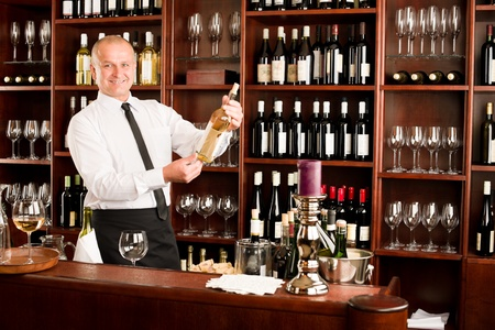 At the bar - waiter hold bottle white wine in restaurant photo