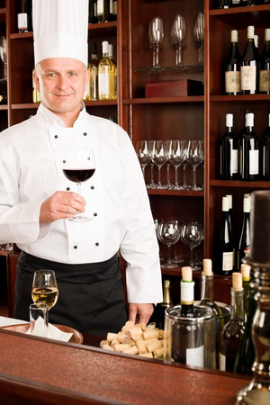 Chef cook hold glass of red wine in restaurant bar photo