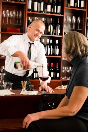 behind bars: Wine bar professional waiter serve glass senior woman smiling