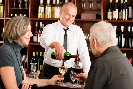 wine tasting: Wine bar senior couple enjoy drink professional barman pour glass