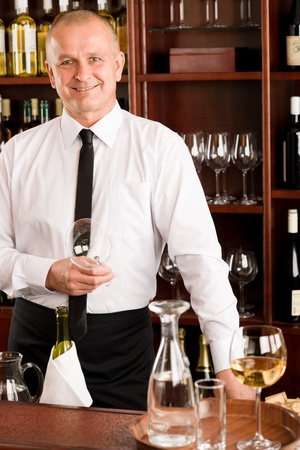 At the bar - waiter hold bottle white wine in restaurant photo