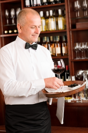 Wine bar waiter mature serving on tray glass olives restaurant photo