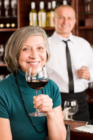 Wine bar senior woman enjoy wine glass in front of bartender photo