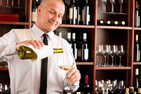 Wine bar happy waiter pour white wine in glass restaurant photo