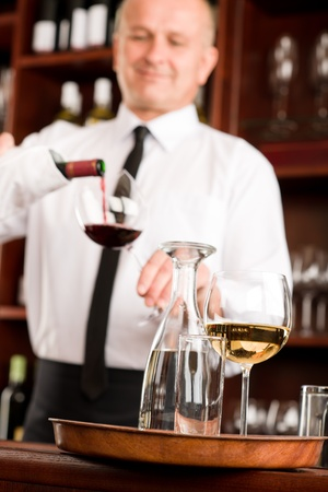 tasting: At the bar - waiter pour red wine in glass restaurant