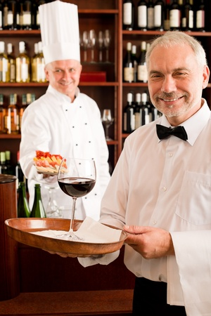 Chef cook with tapas waiter serve on tray in restaurant photo