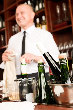 Wine bar bottles close-up waiter clean glass in restaurant photo