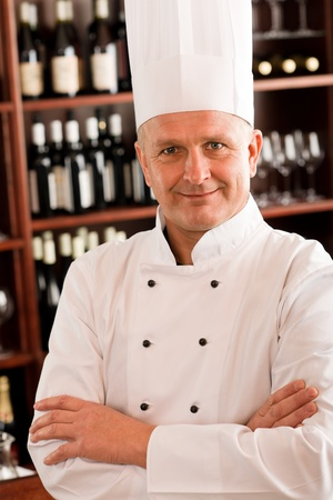 Chef cook confident professional posing in restaurant cross arms photo