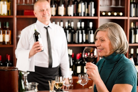 tasting wine: Wine bar senior woman enjoy wine glass in front of bartender