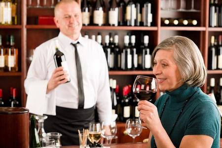 weinverkostung: Wine bar senior woman genie�en Weinglas vor Barkeeper