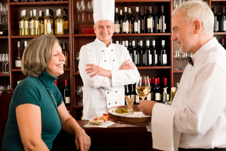 degustation: Restaurant manager smiling with staff at wine bar