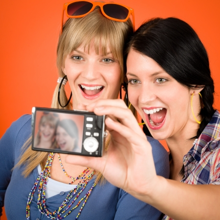 Two young woman friends taking picture with camera orange background photo