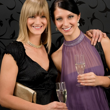 Two women friends party dress hold champagne glass smiling together photo