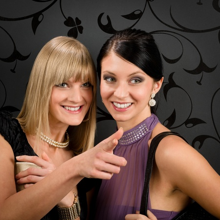 Two women friends party dress pointing at something smiling together photo