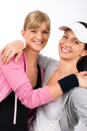 two women hugging: Two women friends sport outfit hugging smiling isolated portrait Stock Photo