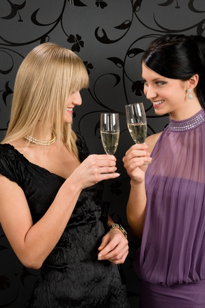 Two women friends party dress toast champagne glass smiling together photo