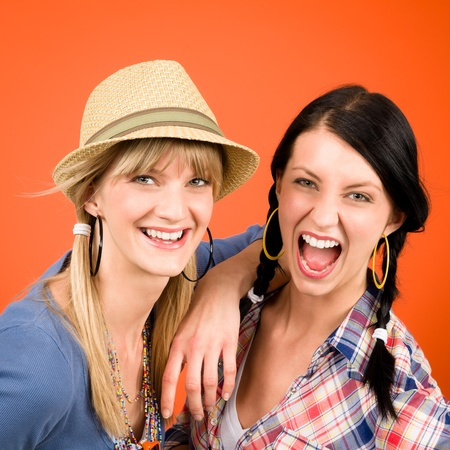 Two woman friends young crazy smile portrait on orange background photo