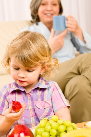 Little girl eat strawberry fruit with grandmother relaxing on sofa photo
