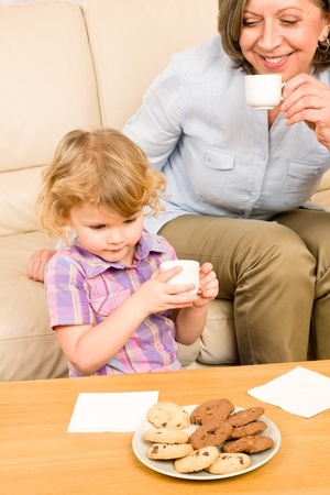 Little granddaughter with grandmother eat cookies drink tea cup together Stock Photo - 12079924