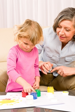 Granddaughter with grandmother play making handprints painting at home Stock Photo - 12079927