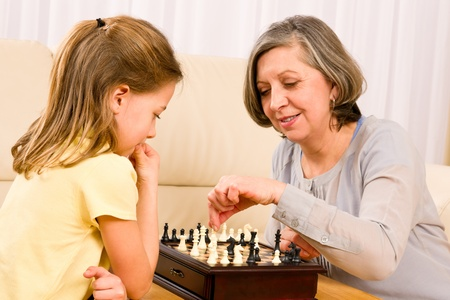 Grandmother and young girl playing chess together at home photo