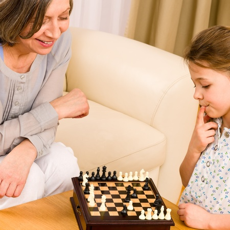 Young girl playing chess with grandmother together at home Stock Photo - 12079919