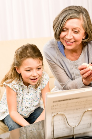 Grandmother teach young girl learn music notes play flute smiling Stock Photo - 12079922