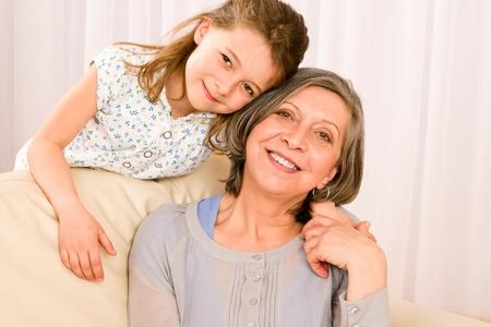 abuela: Abuela con la chica sonriente relajarse juntos en el sofá