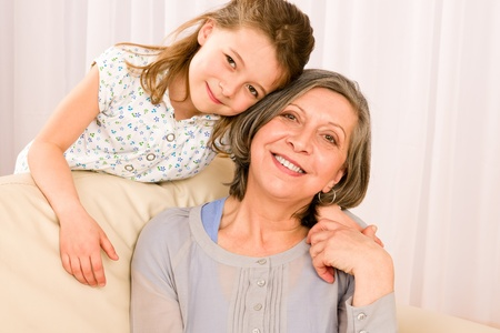 granddaughter: Grandmother with young girl smiling relax together on sofa Stock Photo