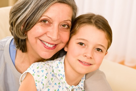 grandmother grandchild: Grandmother and granddaughter hugging together smiling close-up portrait Stock Photo