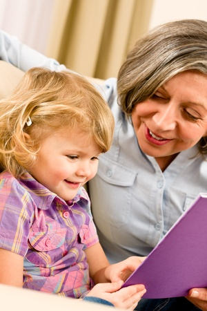 Grandmother and little girl reading book happy together at home Stock Photo - 12079942